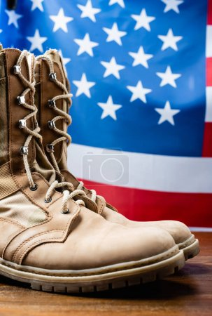 military boots near american flag on blurred background