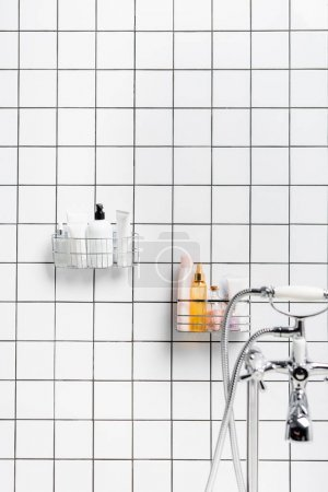 Photo for Toiletries near faucet on blurred foreground in modern white bathroom - Royalty Free Image