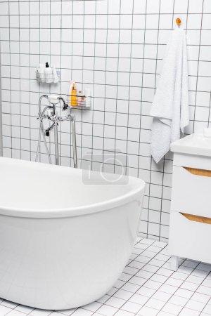 Toiletries near towel and bathtub in modern white bathroom