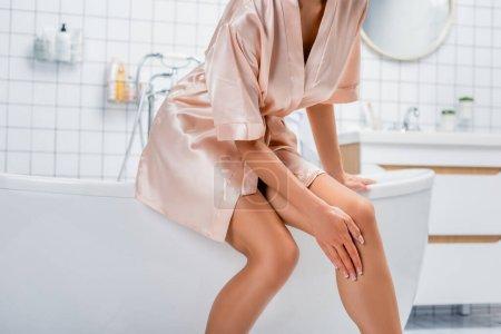 Cropped view of woman in satin bathrobe touching leg in bathroom