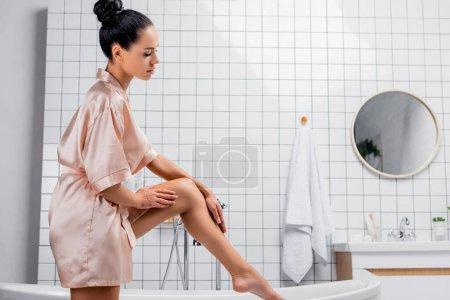 Photo pour Vue latérale de la jeune femme en peignoir satiné touchant la jambe près de la baignoire - image libre de droit