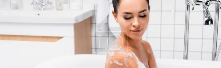 Young woman looking at wet shoulder in foam in bathtub, banner