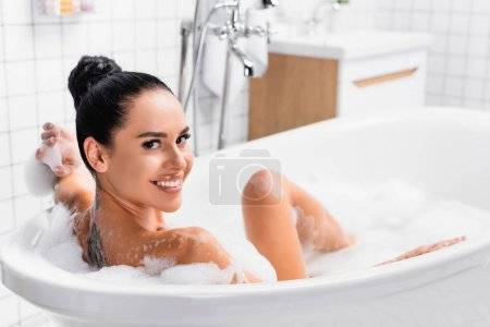 Tattooed woman smiling at camera while taking bath on blurred background