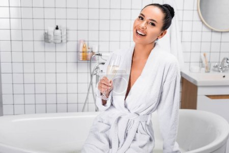 Smiling woman in bathrobe holding glass of champagne in bathroom