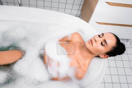 Brünette Frau nimmt Bad mit Seifenlauge zu Hause
