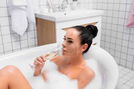 Photo for Brunette woman drinking champagne in bathtub with foam - Royalty Free Image