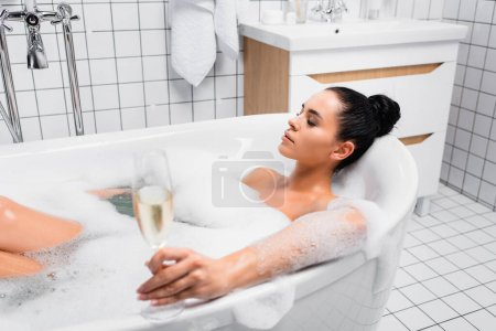 Photo for Young woman with closed eyes holding glass of champagne on blurred foreground while taking bath - Royalty Free Image