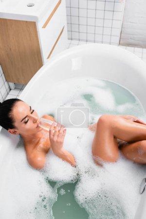 Hochwinkelaufnahme einer brünetten Frau, die Champagner in einem Bad mit Schaum trinkt
