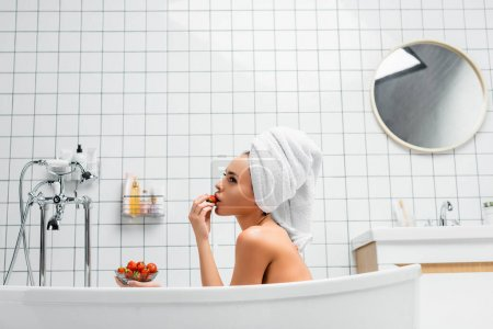 Photo for Side view of young woman with towel on head eating juicy strawberry in bathtub at home - Royalty Free Image