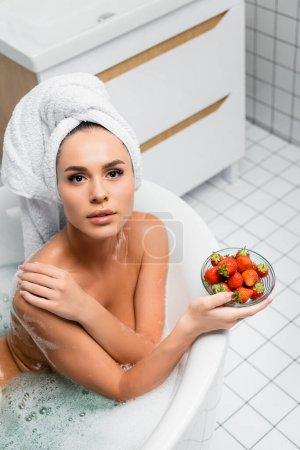 Young woman with towel on head looking at camera while holding bowl of strawberries in bathtub
