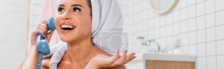 Cheerful woman with towel on head talking on telephone in bathroom on blurred background, banner