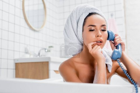 Young woman with towel on head and finger near lips talking on telephone in bath on blurred foreground