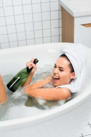 Excited woman with towel on head holding bottle of champagne in bath with foam