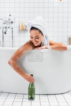 Smiling woman with towel on head taking bottle of champagne while bathing