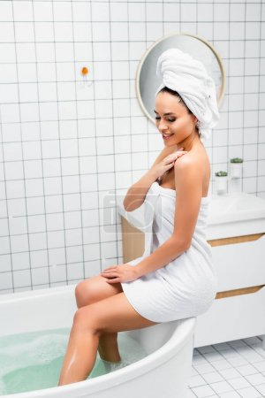 Smiling woman in towels sitting on bathtub with water