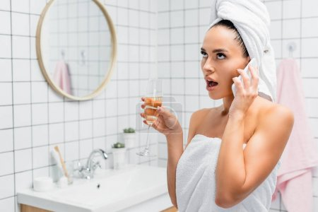 Shocked woman in towels talking on smartphone while holding glass of champagne in bathroom on blurred background