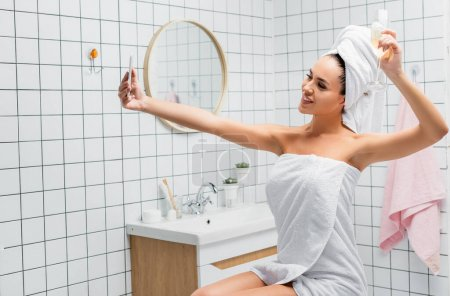 Photo for Smiling woman in towels holding glass of champagne while taking selfie in bathroom - Royalty Free Image