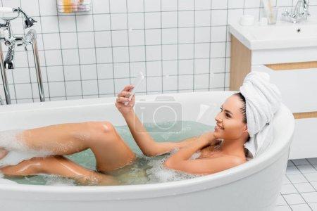 Photo pour Femme souriante prenant selfie dans la baignoire à la maison - image libre de droit