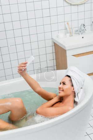 Young woman with towel on head taking selfie with smartphone while taking bath