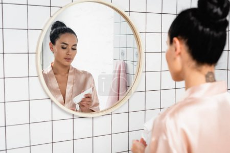 Young woman holding tube with cosmetic cream near mirror in bathroom