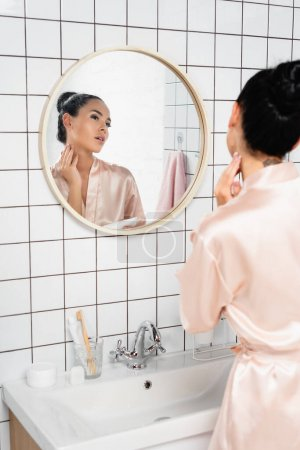 Brünette Frau trägt kosmetische Creme in der Nähe von Waschbecken und Spiegel im Badezimmer auf