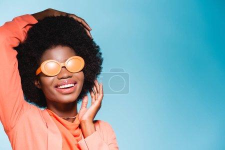 Photo pour Smilig afro-américaine jeune femme en tenue élégante orange isolé sur fond bleu - image libre de droit