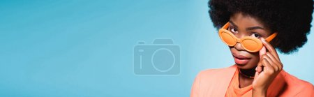 african american young woman in orange stylish outfit isolated on blue background, banner