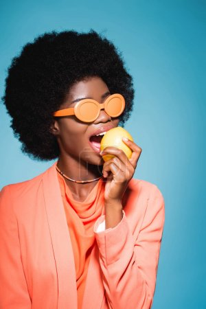 african american young woman in orange stylish outfit biting lemon isolated on blue background