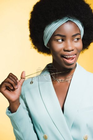 Photo for African american young woman in blue stylish outfit showing necklace isolated on yellow - Royalty Free Image