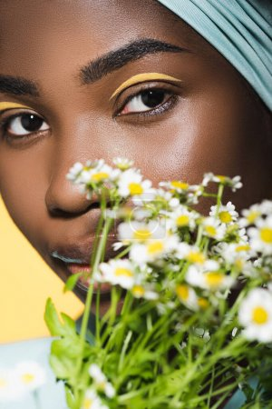 Photo for Closeup of african american young woman with chamomile bouquet isolated on yellow - Royalty Free Image