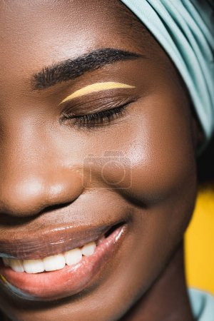 closeup of smiling african american young woman isolated on yellow