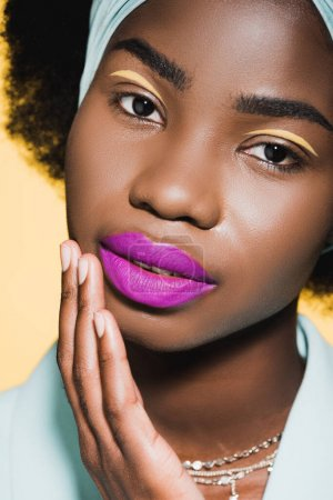 african american young woman with purple lips isolated on yellow