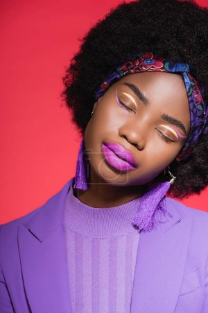african american young woman with closed eyes in purple stylish outfit isolated on red