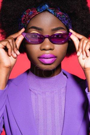 Photo pour Afro-américaine jeune femme en violet tenue élégante et lunettes de soleil isolées sur rouge - image libre de droit