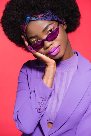 african american young woman in purple stylish outfit and sunglasses isolated on red