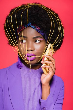 african american young woman in purple stylish outfit with yellow strings on face holding smartphone isolated on red
