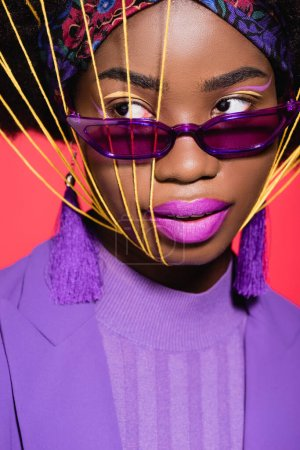 Photo for African american young woman in purple stylish outfit and sunglasses with yellow strings on face isolated on red - Royalty Free Image