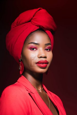 african american young woman in red stylish outfit and turban isolated on black