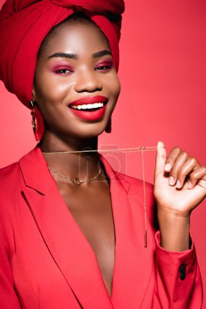 smiling african american young woman in stylish outfit and turban holding necklace isolated on red