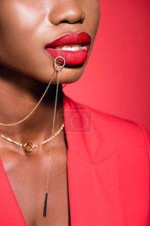 Photo pour Vue recadrée de la jeune femme afro-américaine en tenue élégante tenant collier dans la bouche isolé sur rouge - image libre de droit