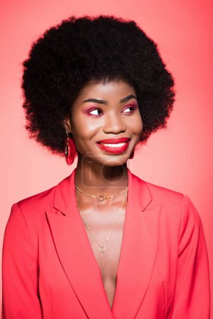 happy african american young woman in stylish outfit isolated on red