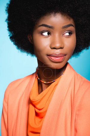 african american young woman in orange stylish outfit isolated on blue