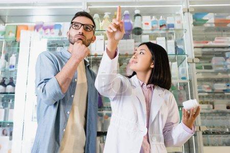 Photo pour Vue à angle bas du pharmacien asiatique pointant avec le doigt et regardant client coûteux dans les lunettes dans la pharmacie - image libre de droit