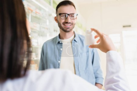 Photo for Cheerful customer looking at pharmacist holding bottle with medication on blurred foreground - Royalty Free Image