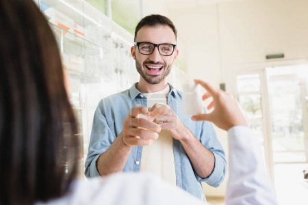 Photo for Excited man in eyeglasses looking at pharmacist holding bottle with medication on blurred foreground - Royalty Free Image