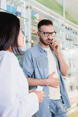 Photo for Customer in eyeglasses talking on smartphone near asian pharmacist on blurred foreground - Royalty Free Image