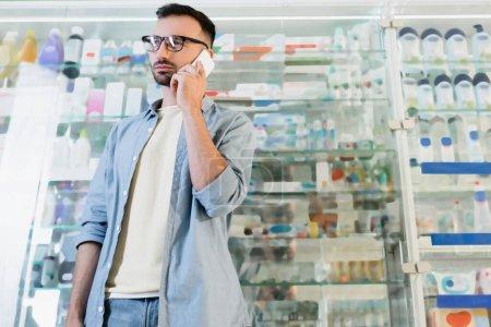 man in eyeglasses talking on mobile phone in drugstore