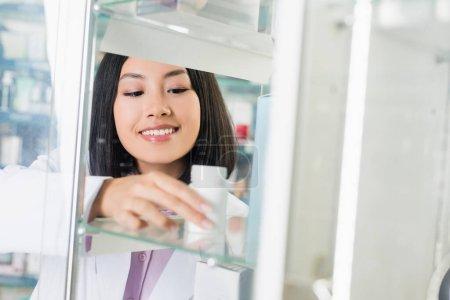 cheerful asian pharmacist in white coat taking bottle with medication on glass shelf