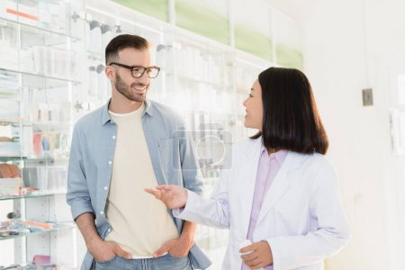 Photo for Cheerful asian pharmacist in white coat pointing with finger while talking with customer - Royalty Free Image