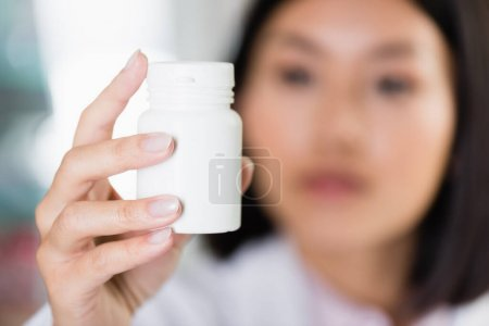 bottle with pills in hand of asian pharmacist on blurred background